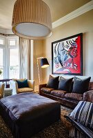 Ottoman, cushions arranged on leather sofa below modern artwork on wall