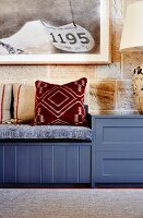 Patterned cushions on blue bench against stone wall