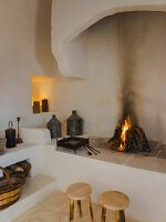 Two rustic wooden stools in front of open masonry fireplace with niches and platforms in restored Apulian trullo