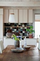 View across wooden table to kitchen counter with multicoloured ceramic-tiled splashback