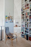 Retro armchair next to floor-to-ceiling bookcase