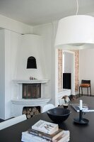 White pendant lamp above black table in front of corner fireplace with firewood niche