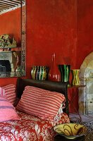 Vintage-style interior with red walls, red and white striped cushions on daybed and collection of colourful vases on side table