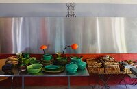 Green ceramic crockery on metal table and stacked basket trays on side table below stainless steel cladding on wall