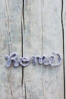 Crocheted cord arranged to spell 'Home' on vintage wooden surface