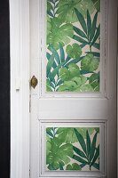 White vintage interior door with panels covered in green leaf-patterned wallpaper