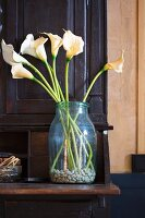 White calla lilies and pebbles in vintage jar on shelf of wooden dresser