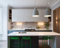 Kitchen with white counter-height table and green-painted bar stools in traditional interior