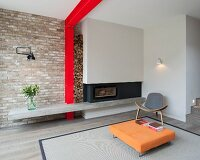 Low orange coffee table on rug and designer easy chair in front of grey fireplace; red steel structure and stacked firewood against brick wall