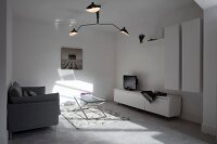 Three-armed designer lamp in white minimalist living room with patterns of light and shade on floor