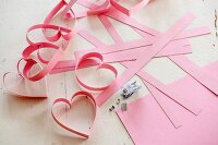 Making a garland of paper love-hearts