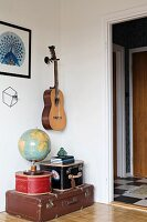 Globe on top of stacked antique suitcases below guitar mounted on wall