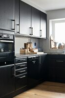 Black L-shaped kitchen units with window and serving hatch