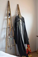 Jewellery and clothing hung on ladder-style wooden frames leant against wall