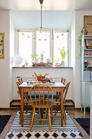 Wooden dining set below window