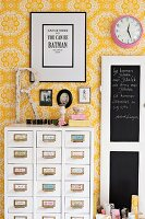 White chest of drawers with labelled handles against yellow and white floral wallpaper