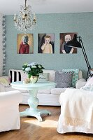 Round table, white armchairs and comfortable sofa below portraits of children on patterned wallpaper