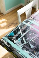 Various layers and splotches of paint on table top next to backrest of white chair