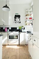 White kitchen with rustic wooden floor and black and white Pop-Art poster