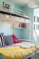 White metal bunk beds with ladder decorated with fairy lights in teenagers' bedroom with pale blue walls