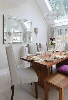 Place settings on elegant wooden table, bench, pale grey upholstered chairs, mirror on wall and skylight