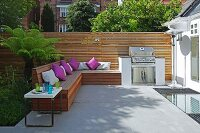 Purple cushions on fitted wooden bench and barbecue on sunny terrace with modern screen
