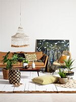 Patterned wicker stool, coffee table, pale brown sofa and house plants