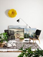 Various armchairs, retro standard lamp, house plants and yellow artwork on wall