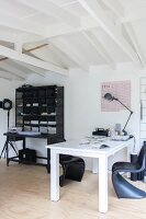 White desk and classic black shell chairs next to black modern bureau
