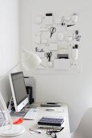 Monitor and white table lamp on white desk in corner below white, plastic retro organiser on wall