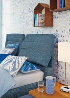 Double bed and headboard upholstered in denim below small, house-shaped shelving modules on wallpaper with blurry pattern
