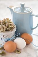 Hen's eggs with a ribbon, a hydrangea and a blue coffee pot on a marble surface