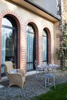 Delicate metal furniture and wicker chair on gravel terrace outside elegant country house with arched windows