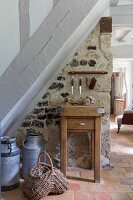 Chopping block and old milk churns against stone wall