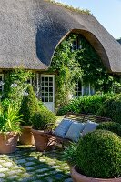 Thatched house and seating area on paved courtyard