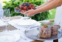Glass dish of fresh berries held in hands and preserving jars on tray on garden table
