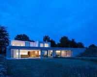 Modern architect-designed house with flat roofs and large windows at twilight