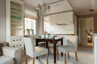 Pale upholstered dining chairs and dark brown wooden table in open-plan kitchen