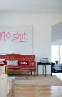 Red, antique sofa, rustic wooden table and delicate side table below artwork with motto on wall of open-plan living area
