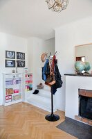 Bags hanging on coat stand next to foot of staircase in modern interior with open fireplace