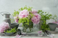 Peonies and lady's mantle in glass jug and tin utensils