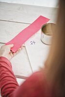 Tin can, sticker and pink paper in girl's hand for making DIY Advent calendar