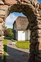 View of holiday home seen through stone archway