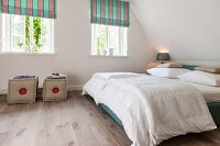 Bedroom in modern rustic style; double bed with white bed linen under sloping ceiling and pouffes below striped Roman blinds on windows