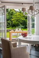 Pale, loose-covered armchair at white table below chandelier in front of open terrace doors with view of terrace