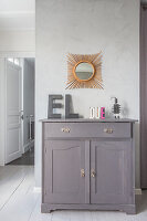 Decorative letters on top of rustic grey cabinet below sunburst mirror on stucco lustro wall