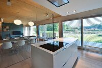 Designer kitchen island next to glass partition with view of dining area and louvre blinds on glass wall