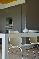 View across edge of table to white shell chairs and fitted kitchens