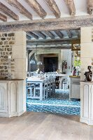 View from dining room into country-house kitchen with blue and white ornamental floor tiles