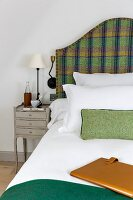 Delicate grey bedside cabinet with drawers next to double bed with curved tartan headboard